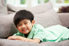 Young Chinese Boy Relaxing On Sofa At Home. Smiling Stock Image