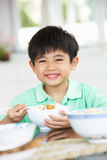 Young Chinese Boy Sitting At Home Eating Meal Stock Photos