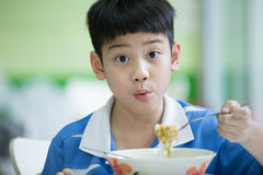 Young Chinese Boy Sitting At Home Eating Meal Royalty Free Stock Photo