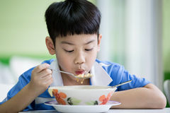 Young Chinese Boy Sitting At Home Eating Meal Stock Images