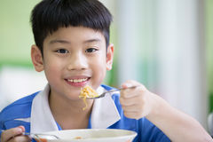 Young Chinese Boy Sitting At Home Eating Meal Stock Photo