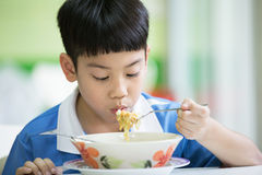 Young Chinese Boy Sitting At Home Eating Meal Royalty Free Stock Photos