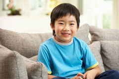 Young Chinese Boy Sitting On Sofa At Home Royalty Free Stock Image