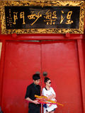 Young Chinese Couple going praying in Temple Stock Image