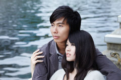 Young Chinese couple in love on romantic date. Young Chinese couple looking faraway. Shot outdoors. Romance and love Stock Images