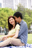 Young Chinese Couple Relaxing In Park Together Stock Photo