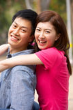 Young Chinese Couple Relaxing In Park Together Royalty Free Stock Photo