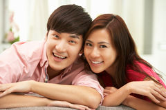 Young Chinese Couple Relaxing On Sofa At Home Royalty Free Stock Photo