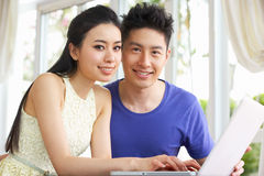 Young Chinese Couple And Using Laptop At Home Royalty Free Stock Photography