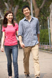Young Chinese Couple Walking In Park Stock Photography