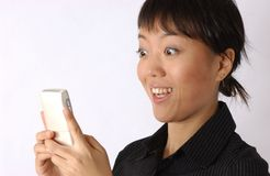 Young chinese girl. Seems very happy to watch her mobile or any handset device royalty free stock photo
