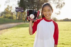 Young Chinese girl holding baseball in mitt looks to camera stock images