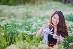Young Chinese girl pouring tea in flowering meadow Royalty Free Stock Photos