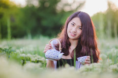 Young Chinese girl pouring tea in flowering meadow Royalty Free Stock Photo