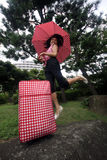 Young Chinese jumping with umbrella and suitcase Stock Photo