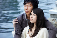 Young Chinese lovers embracing by river Royalty Free Stock Image