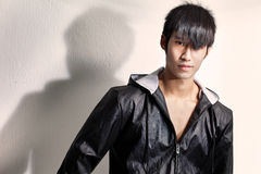 Young, chinese male model in black jacket. Fashion shot of a young and muscular Chinese male model wearing a black jacket and looking into camera. Lit with Royalty Free Stock Photos