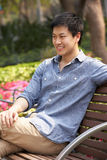 Young Chinese Man Relaxing On Park Bench Royalty Free Stock Photo