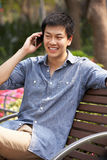 Young Chinese Man Relaxing On Park Bench Stock Images