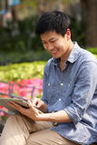 Young Chinese Man Using Digital Tablet Royalty Free Stock Image