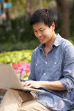 Young Chinese Man Using Laptop Whilst  Relaxing Stock Photos