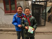 Young Chinese Students. With a school book wearing Chinese student red scarfs standing in a hutong neighborhood Royalty Free Stock Photos
