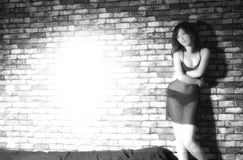 Young Chinese woman. A young Chinese woman model posing near a brickwall lit up in bright light Royalty Free Stock Photos