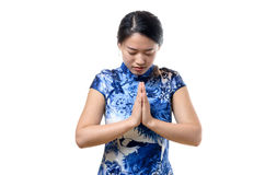 Young Chinese woman bowing her head. With clasped hands in a traditional greeting or prayer, upper body isolated on white royalty free stock image