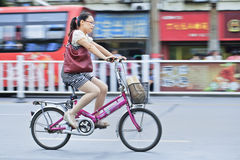 Young Chinese woman cycling. XIANG YANG-CHINA-JULY 1, 2012. Woman on a bicycle on July 1, 2012 in Xiang Yang. 430 million owners of bicycles in China represent Royalty Free Stock Images