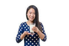 Young Chinese woman drinking a glass of milk Stock Photo