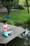 Young chinese woman practicing yoga outdoor Stock Photo