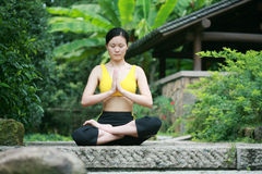 Young chinese woman practicing yoga outdoor Stock Photos