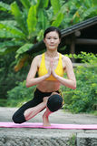 Young chinese woman practicing yoga outdoor Stock Photography