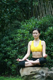 Young chinese woman practicing yoga outdoor Royalty Free Stock Images