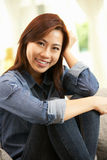 Young Chinese Woman Relaxing On Sofa At Home Royalty Free Stock Image