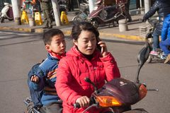Young chinese woman riding a scooter talking in mobile cell phone with a child on the back seat stock photo