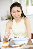 Young Chinese Woman Sitting At Home Eating Meal Stock Photos