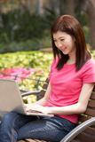 Young Chinese Woman Using Laptop Whilst  Relaxing Stock Image
