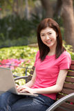 Young Chinese Woman Using Laptop Whilst  Relaxing Royalty Free Stock Images