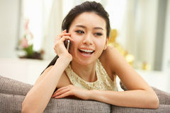 Young Chinese Woman Using Mobile Phone At Home Royalty Free Stock Photography