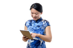 Young Chinese woman using a tablet pc. Surfing the internet with her finger smiling at information on the screen, upper body isolated on white royalty free stock photos