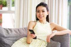 Young Chinese Woman Watching TV On Sofa At Home. Young Chinese Woman Sitting And Watching TV On Sofa At Home Royalty Free Stock Photography