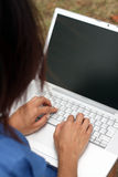 Young Chinese woman writing on a laptop outdoors Stock Photography