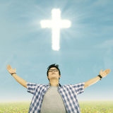 Young christian man. Young casual man standing with a glowing cross above his head stock photo