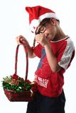 Young christmas boy. Young boy with santa hat and glasses stealing candy from Christmas basket royalty free stock photography