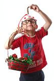 Young christmas boy. Young boy with santa hat and glasses stealing candy from Christmas basket stock image