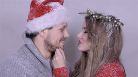 Young Christmas couple enjoying snow over white background stock video footage