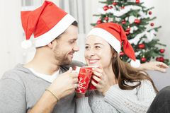 Young christmas couple happy on sofa royalty free stock photo