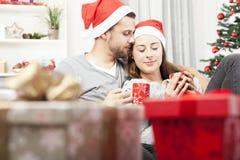 Young christmas couple relaxing on sofa Stock Photos