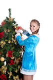 Young christmas girl decorate new year fir tree. Attractive christmas girl decorate new year fir tree - look at you Royalty Free Stock Photography